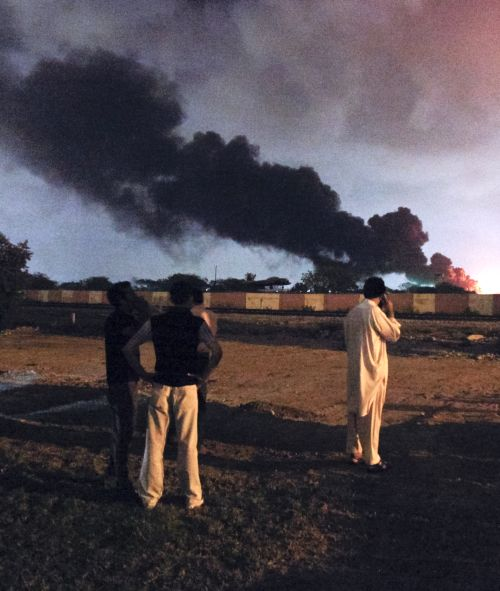 Men watch as a plume of smoke rises from the Mehran naval aviation base after it was attacked by militants in Karachi on May 22, 2011