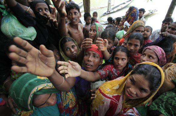 People wait for food to be distributed by local organisations as they take shelter at a school building in flood-hit Sylhet in Bangladesh on June 30, 2012