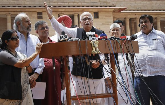 Senior BJP leader LK Advani speaks to the media while party president Gadkari, Leader of Opposition Sushma Swaraj and other leaders look on, in New Delhi