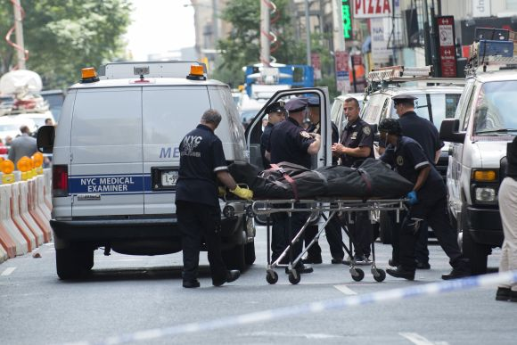 The body of a shooting victim is moved by the New York City Coroner near the site of the Empire State building where a gunman opened fire shooting several bystanders before being killed by police