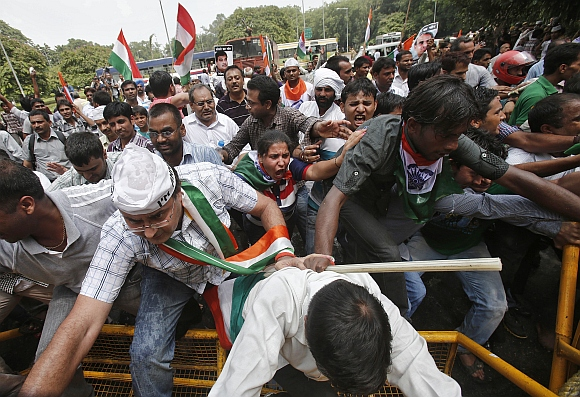 Supporters of veteran Indian social activist Anna Hazare climb over a police barricade during a protest against corruption near the residence of Prime Minister Manmohan Singh in New Delhi