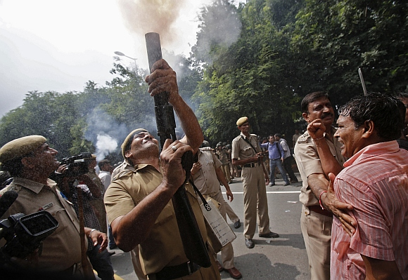 A police officer fires a teargas shell to disperse Anna supporters near the PM's residence