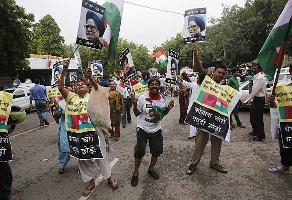 Anna supporters shout slogans as they hold posters of Prime Minister Manmohan Singh