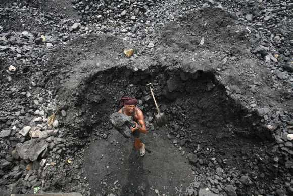 A labourer loads coal onto a truck at a coal yard on the outskirts of Jammu