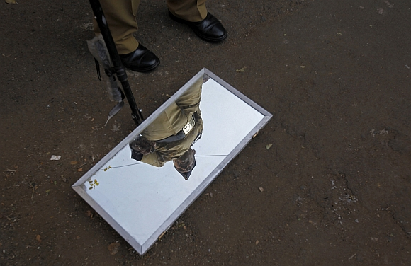 A policeman's reflection is seen in a mirror used to check vehicles for explosives outside the Bombay high court before the delivery of a judgement for Ajmal Kasab