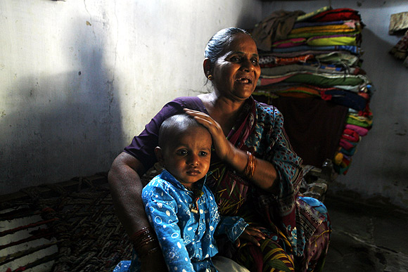 Hajira Sheikh, a riot survivor holds her grandson at her residence in the rebuilt Naroda Patiya