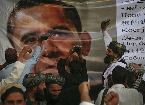 Men place slippers on an image United States President Barack Obama during an anti-US demonstration in Quetta