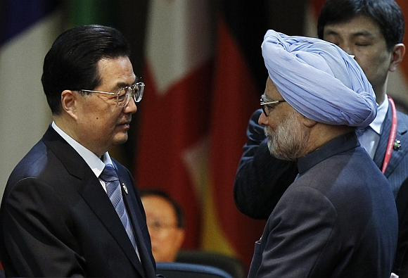 China's President Hu Jintao talks to Prime Minister Manmohan Singh at a plenary session during the Nuclear Security Summit at the Convention and Exhibition Center in Seoul