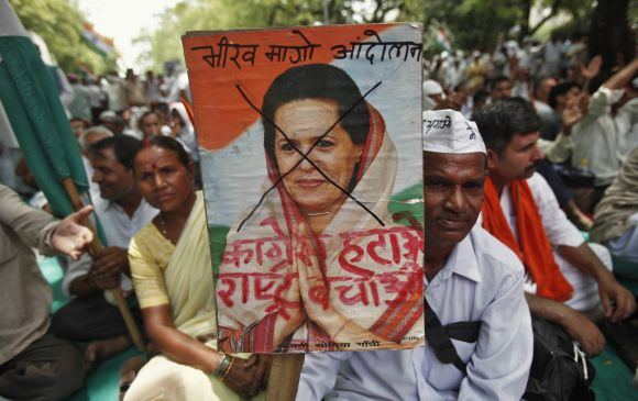 A supporter of social activist Anna Hazare holds up a poster of Congress chief Sonia Gandhi during an anti-corruption demonstration in New Delhi