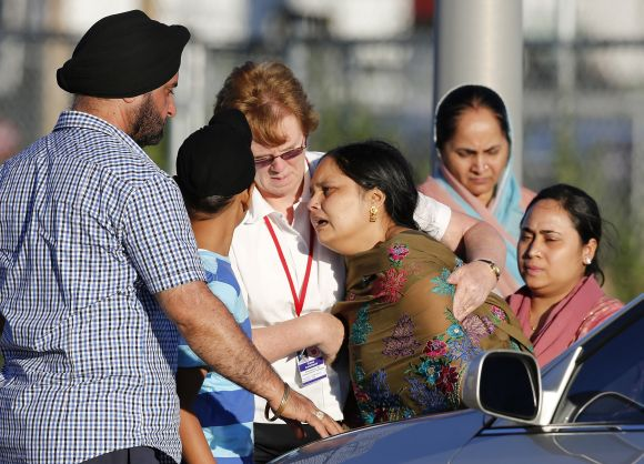 A distraught women is helped to a car outside the Sikh temple in Oak Creek, Wisconsin, after seven people lost their lives in a shooting incident