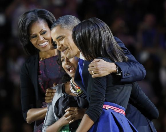 US President Obama hugs his daughters at the victory rally in Chicago
