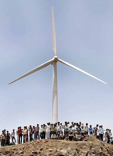 Villagers stand under a power generating windmill turbine at the inauguration of a wind farm at Kalasar, Gujarat