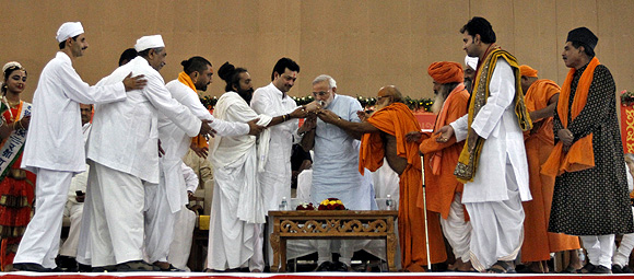 Narendra Modi breaks a fast surrounded by various religious leaders