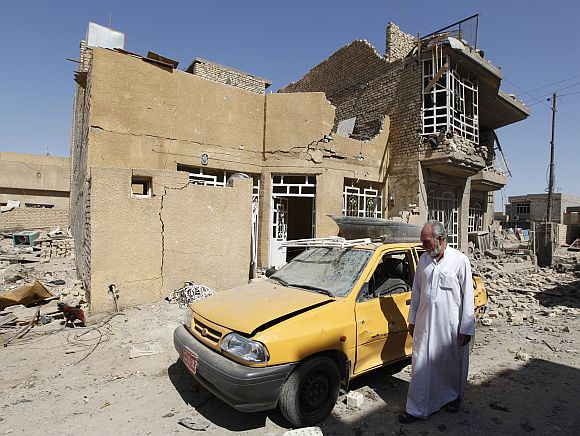 A man walks near the site of a bomb attack in the town of Taji, about 20 km north of Baghdad