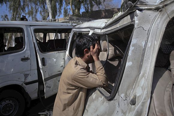 A man weeps next to a damaged vehicle after it was hit by a bomb attack in the outskirts of Peshawar, northwest Pakistan