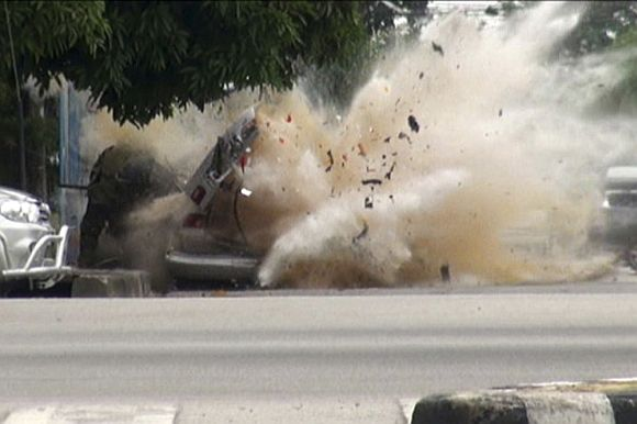 A car bomb explodes as a member of a Thai bomb squad checks it in Narathiwat province, south of Bangkok