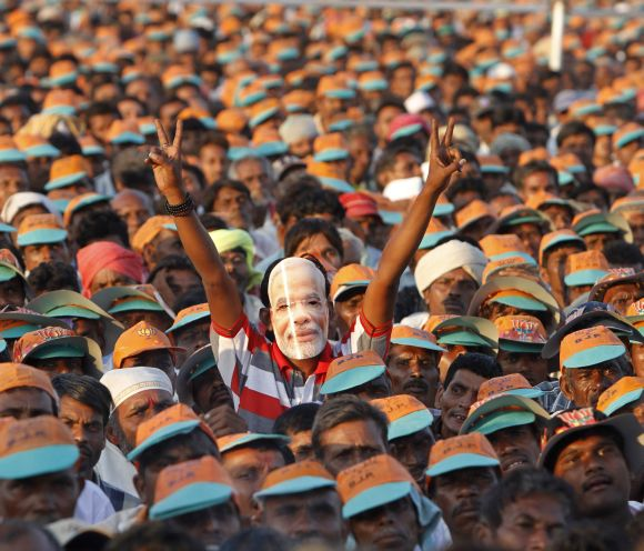A supporter Narendra Modi wears his mask during a campaign rally in Gujarat's Pavagadh town