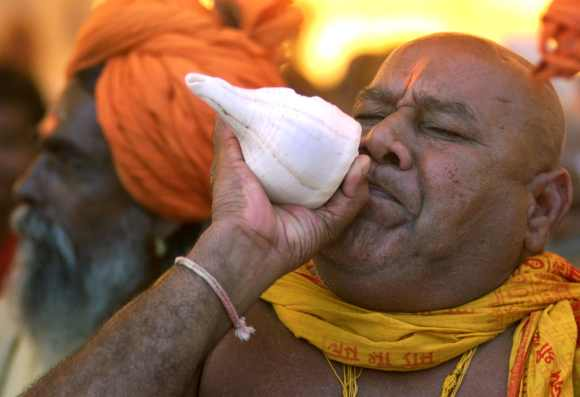 A Hindu priest blows a conch shell in Ayodhya