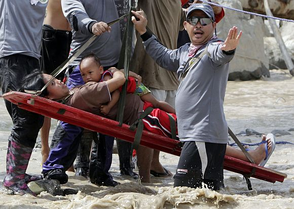 Rescuers evacuate a pregnant woman with her child after they survived flooding in New Bataan town in Compostela Valley in southern Philippines December 6, 2012. Rescuers found the six-months pregnant women from the other side of a river with her one-year-old son after escaping floods that swamped their house after Typhoon Bopha hit land on Tuesday in Compostela Valley