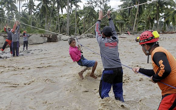 A typhoon victim clings on a rope while being evacuated in New Bataan town in Compostela Valley in southern Philippines December 6