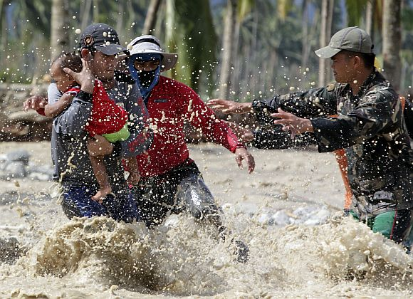 Rescuers evacuate a child who survived flooding with her pregnant mother as they cross a river in New Bataan town, Compostela Valley, southern Philippines December 6, 2012