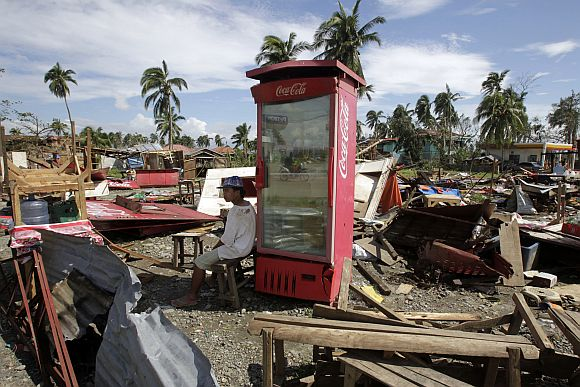 A vendor sits next to a Coca Cola refrigerator amidst destroyed food stalls after Typhoon Bopha hit Compostela Valley, southern Philippines December 5, 2012