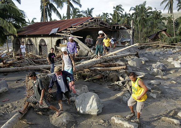 Residents walk among the debris littered on a road after flashfloods brought by Typhoon Bopha in Compostela Valley in southern Philippines