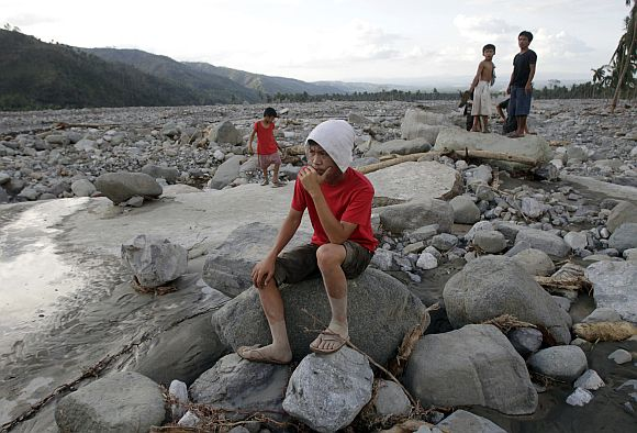 Villagers gather on a destroyed highway littered with rocks and debris after flashfloods brought by Typhoon Bopha in Compostela Valley in southern Philippines