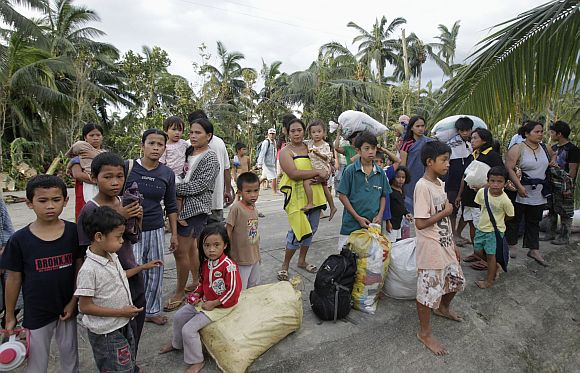 Villagers wait to be evacuated after their homes were swept away by flash floods brought by typhoon Bopha in Compostela Valley, southern Philippines