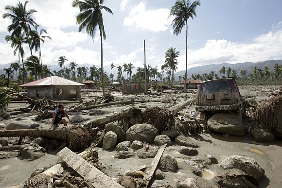 A man walks in an area swamped with debris and mud brought by Typhoon Bopha in New Bataan town in Compostela Valley in southern Philippines December 6