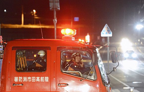 Firefighters persuade residents to evacuate after a strong earthquake hit the area in Rikuzentakata, Iwate prefecture, in this photo taken by Kyodo December 7