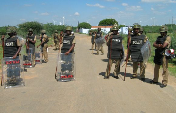 Policemen in riot gear wait outside Idinthakarai village