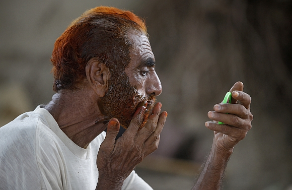 A Muslim man applies henna dye on his beard and hair. According to the seminary, if the hair get red-like colour of henna, then it is permissible