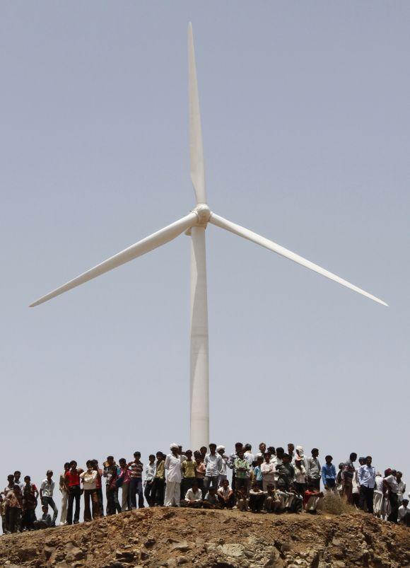 Villagers stand under a power generating windmill turbine at Kalasar village in Gujarat.