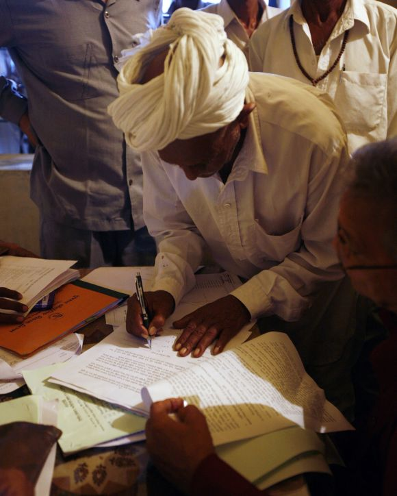 A farmer signs agreement papers to hand over his land to the GIDC (Gujarat Industrial Development Corporation) for the development of an industrial zone at Sanand town in Gujarat