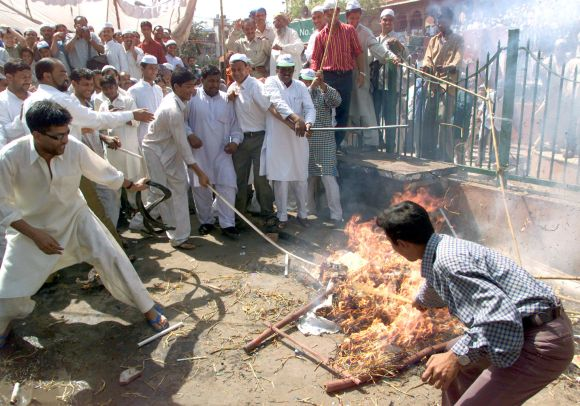 Muslims shout anti-government slogans as they burn an effigy of Narendra Modi