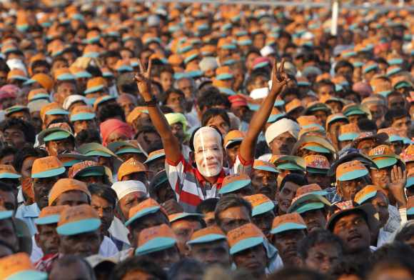 A supporter wears a mask of Modi as he gestures a victory sign during an election campaign rally ahead of the state assembly elections at Pavagadh