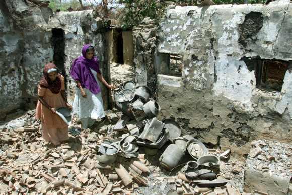 Muslim women Mariba and Zarina Bibi rummage through the debris of their house in Kadwal village in Gujarat on May 12, 2002