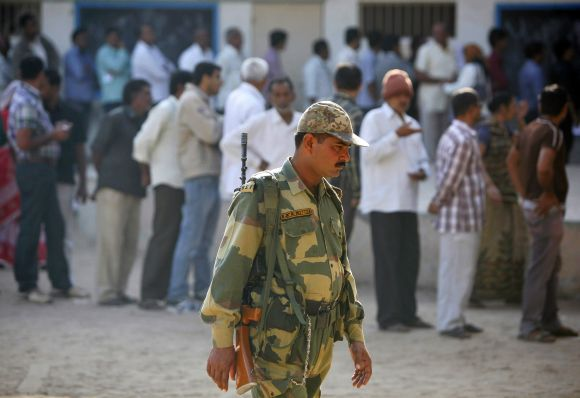BSF personnel patrols as voters stand in queues to cast their ballots outside polling booths in Gujarat's Sanand