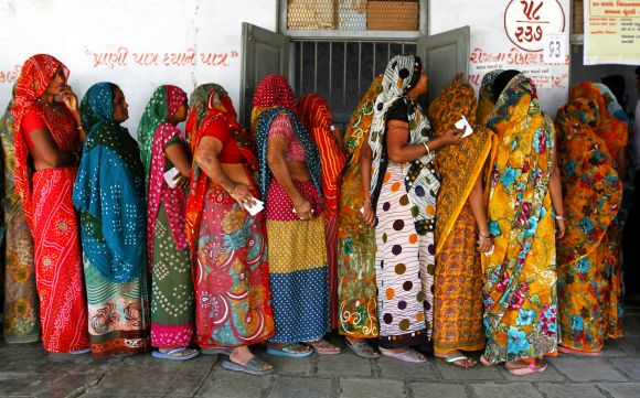 Women wait to vote in Sanand, home of the Tata Nano factory, in Gujarat