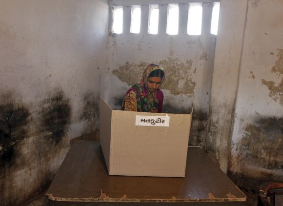 A woman casts her vote at a polling booth in Sanand on Thursday