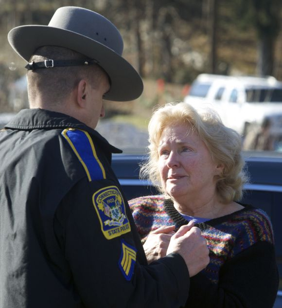 A woman speaks with a Connecticut State Trooper outside Sandy Hook Elementary School after a shooting in Newtown, Connecticut