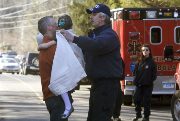 A young girl is given a blanket after being evacuated from Sandy Hook Elementary School following a shooting in Newtown