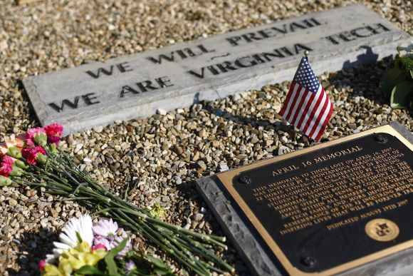 A small United States flag is displayed along with flowers at a plague located in the April 16 memorial on the campus of Virginia Tech in Blacksburg