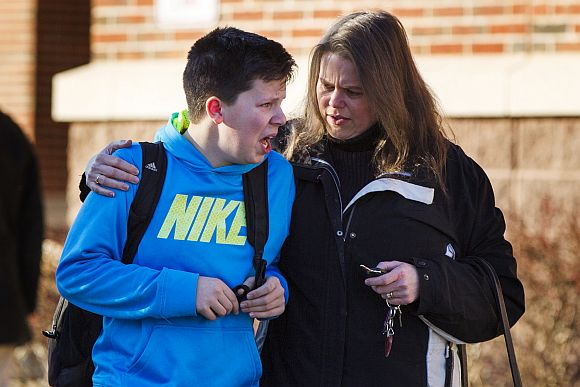 A boy weeps as he is told what happened after being picked up at Reed Intermediate School following a shooting at Sandy Hook Elementary School in Newtown, Connecticut, December 14