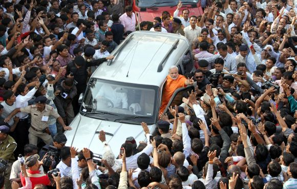 Modi's convoy surrounded by BJP workers, voters and mediapersons as he comes out after casting his vote in Ranip on Monday
