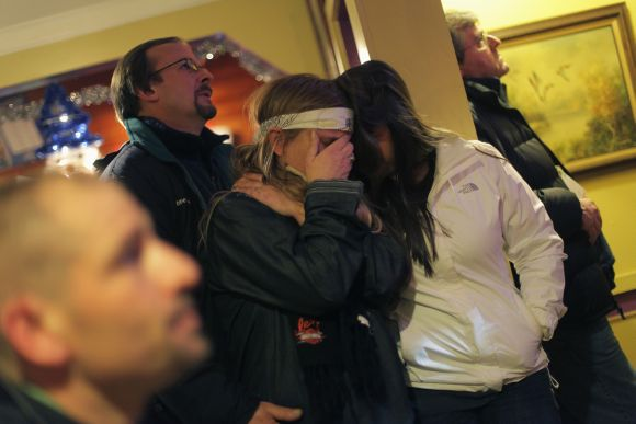 A woman covers her face as she watches U.S. President Obama speak on a television with other patrons, at Church Hill restaurant in Newtown, Connecticut