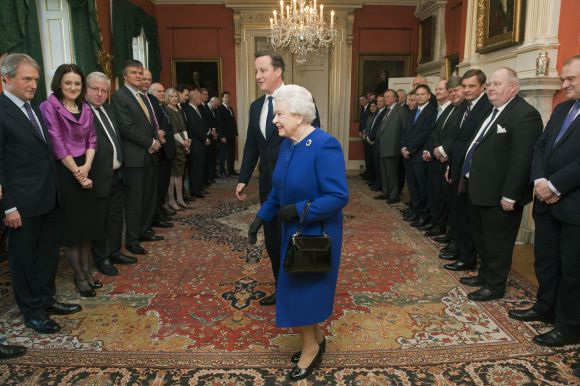 Queen Elizabeth walks with Prime Minister Cameron as members of the cabinet watch at Number 10 Downing Street