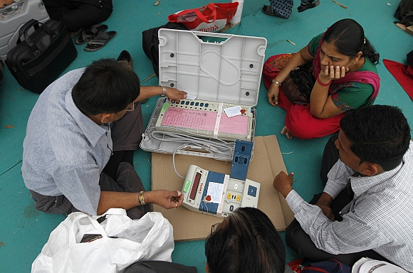 A polling official checks a tag on an EVM at a distribution centre in Sanand, the western