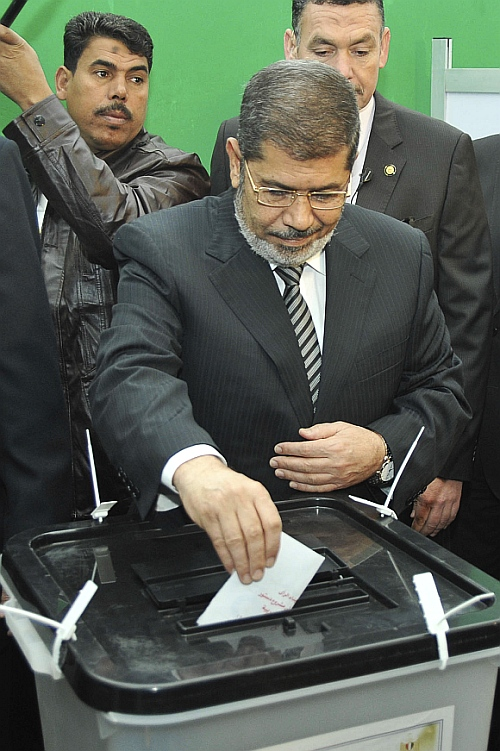 Egypt's President Mohamed Mursi casts his vote during a referendum on the new Egyptian constitution at a polling station in Cairo